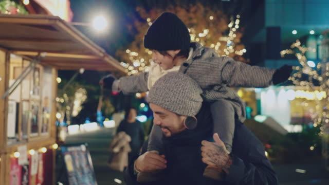 vidéos et rushes de petit garçon chevauchant sur les épaules du père dans le festival de noel - bras en l'air