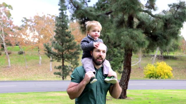 kleiner junge reitet auf den schultern des vaters im park - auf den schultern stock-videos und b-roll-filmmaterial