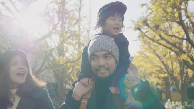 公園で父親の肩に乗っている小さな男の子 - おんぶ点の映像素材/bロール