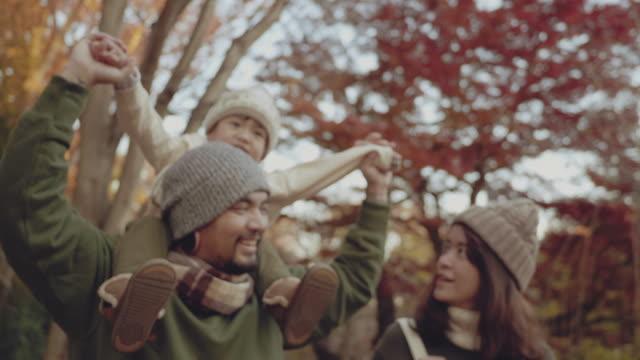 vídeos de stock, filmes e b-roll de garotinho andando sobre os ombros do pai no parque - mãos estendidas