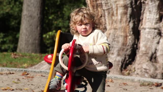 vidéos et rushes de ms little boy riding  rocking horse in park / toronto, ontario, canada - kelly mason videos