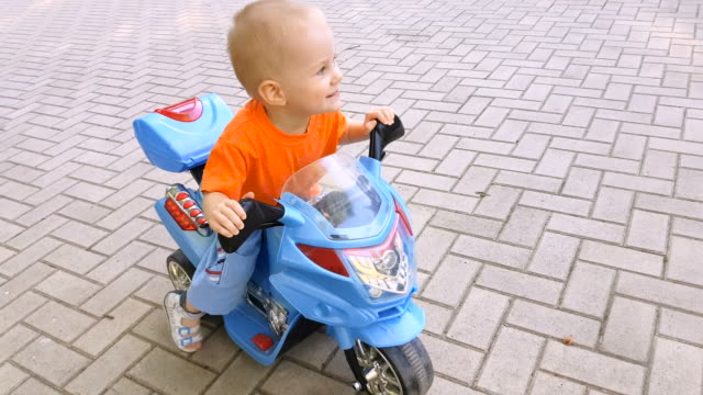 stockvideo's en b-roll-footage met kleine jongen rijden op de motorfiets speelgoed in het park - speelgoed