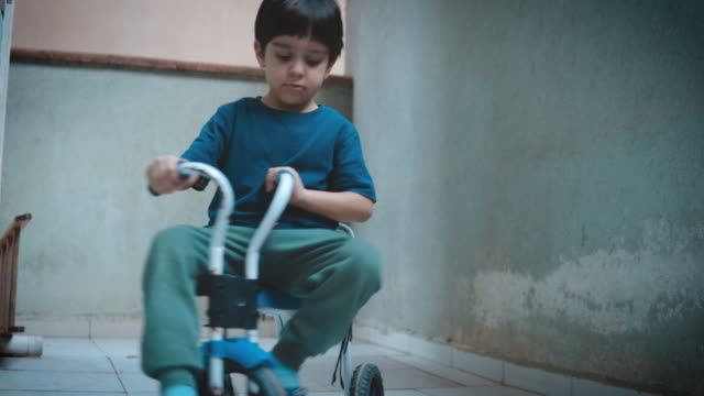 little boy riding tricycle on balcony. feeling lonely because he is not allowed to go outside and play. - tricycle stock videos & royalty-free footage