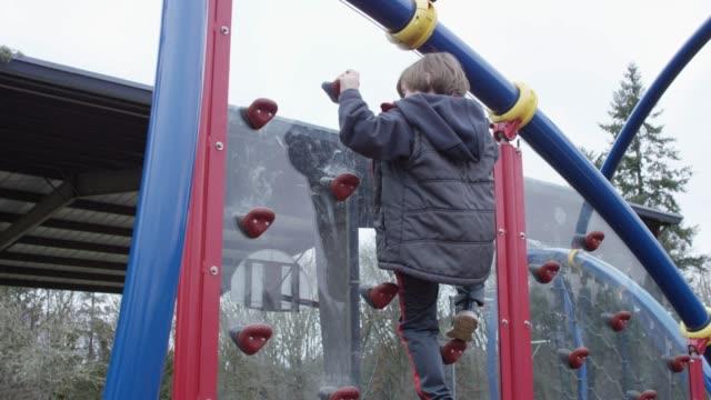 Little Boy Rock Climbing in Playground
