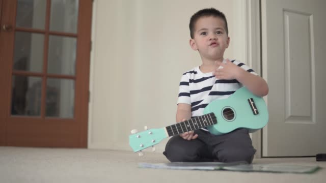 little boy rocking out on a ukelele - guitar stock videos & royalty-free footage