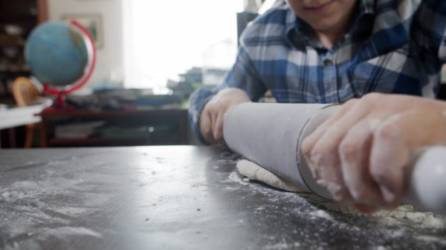 little boy rolling the dough with rolling pin - rolling pin stock videos & royalty-free footage