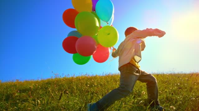 slo mo bambino che corre attraverso il prato soleggiato con un mucchio di palloncini in mano - sunny video stock e b–roll