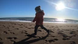 Little Boy running at the beach in winter sunny day.