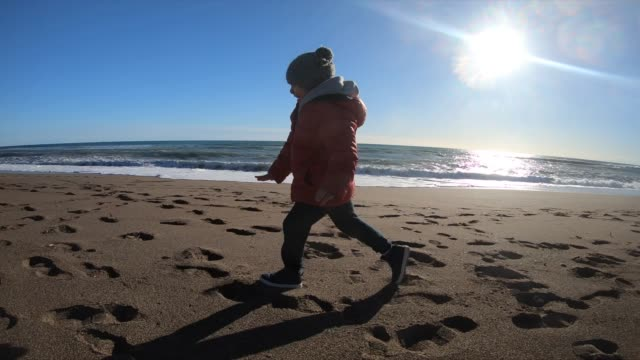 little boy running at the beach in winter sunny day. - autumn stock videos & royalty-free footage