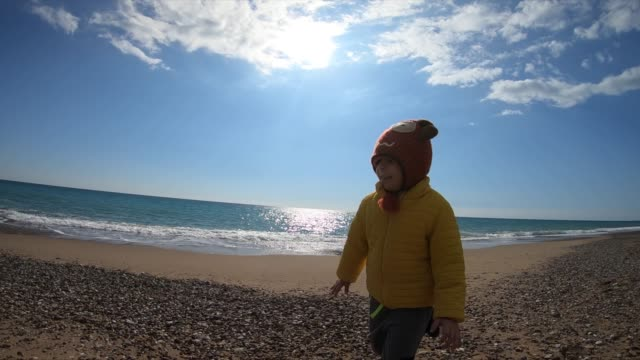 stockvideo's en b-roll-footage met kleine jongen loopt op het strand in de winter zonnige dag. - alleen jongens