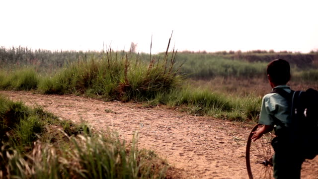 little boy running bicycle rim on country road - hamlet play stock videos and b-roll footage