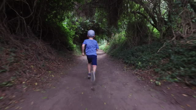 stockvideo's en b-roll-footage met jongetje lopen snel op een bospad - volgen activiteit