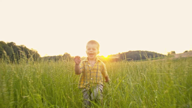 SLO MO Little boy running in the high grass