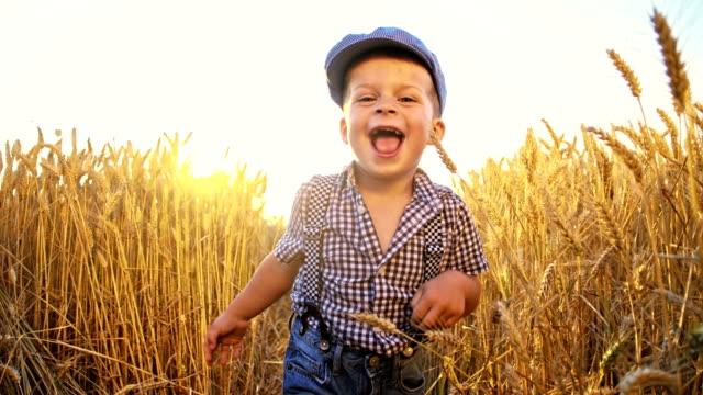 SLO MO Little boy running in wheat field