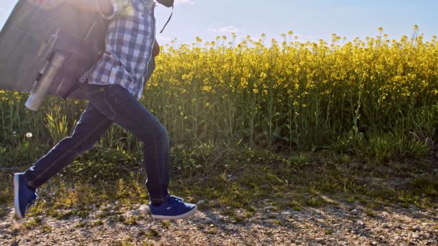 SLO MO liten pojke kör på en grusväg i en jet pack dräkt