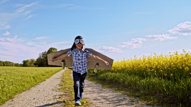 slo mo little boy running on a dirt road in an airplane costume - boys stock videos & royalty-free footage
