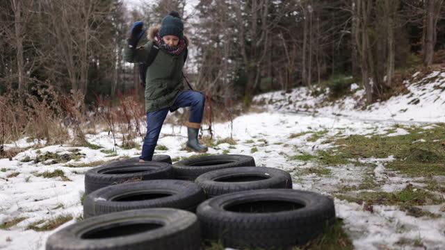 kleiner junge läuft durch reifen hindernisparcours - zufrieden stock-videos und b-roll-filmmaterial