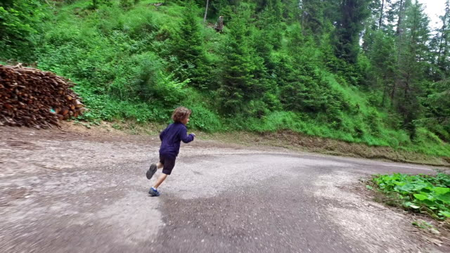 Little boy runs on mountain road - Dolomites