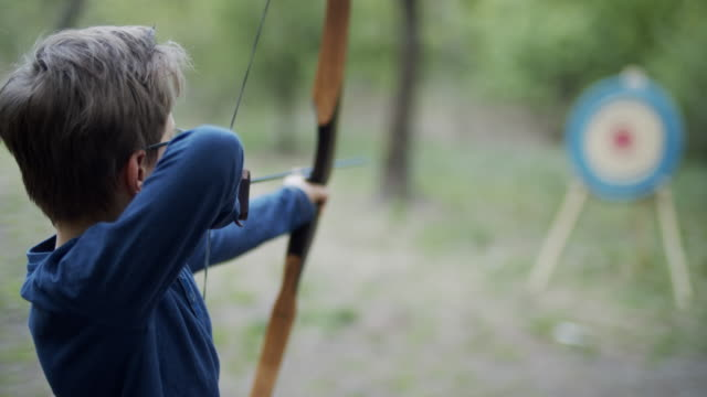 little boy shooting bow in the forest - arrow bow and arrow stock videos & royalty-free footage
