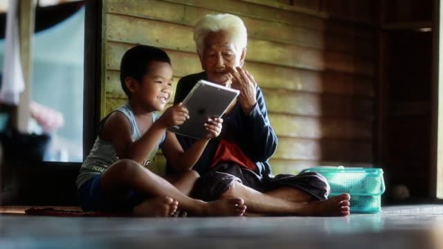Jongen toont iets in Tablet aan zijn grootmoeder