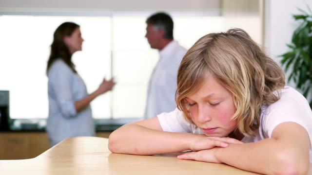 Little boy sighing while listening to his parents