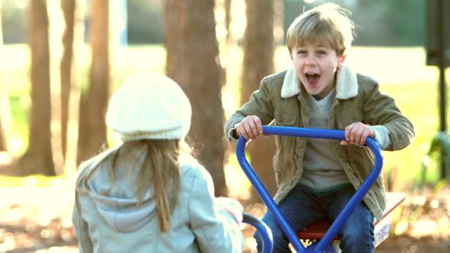 kleiner junge, schwester auf teeter totter - wippe stock-videos und b-roll-filmmaterial