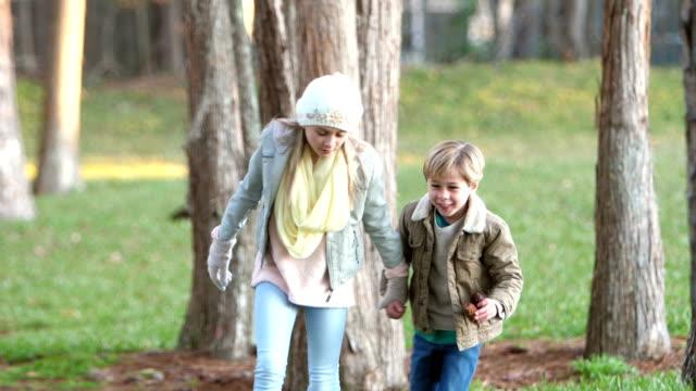 liten pojke, syster promenader i parken plocka upp kottar - gå tillsammans bildbanksvideor och videomaterial från bakom kulisserna