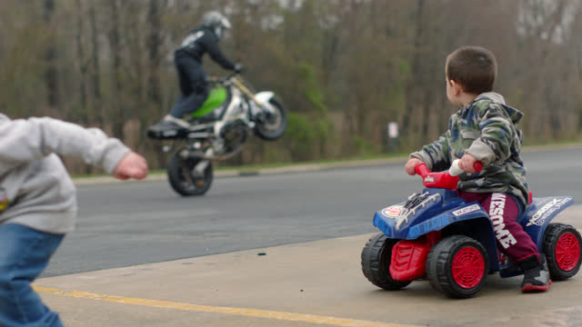 a little boy sits on a child sized ride-on atv and another boy plays with a firetruck while they watch stunt motorcycle riders perform acrobatic stunts - 2 3 anni video stock e b–roll