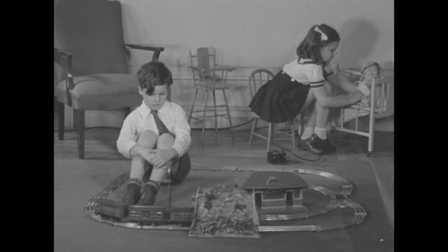 vídeos y material grabado en eventos de stock de ms little boy sits on floor and plays with train set as little girl plays with baby doll in background / note exact year not known - juguete