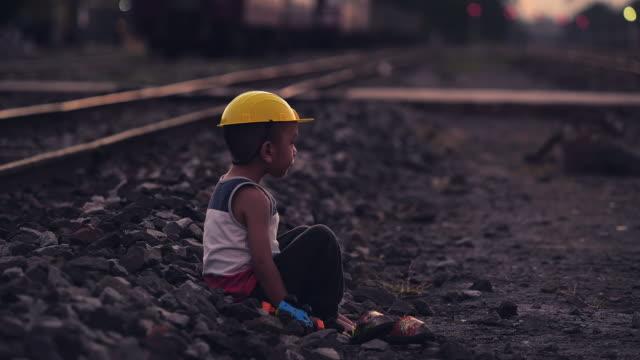 vídeos de stock, filmes e b-roll de menino que senta-se sozinho ao ar livre - estrada de ferro