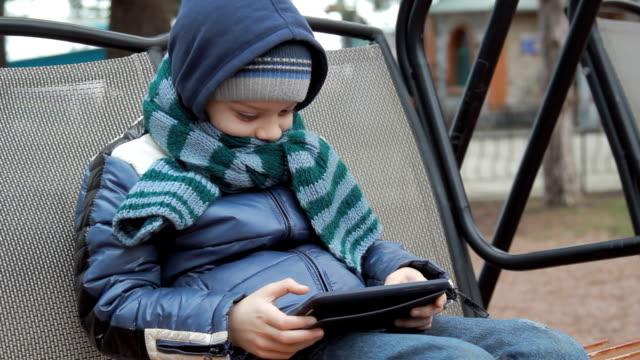 allein kleine junge sitzend auf schaukel mit digitalen tablet - spielzeug stock-videos und b-roll-filmmaterial