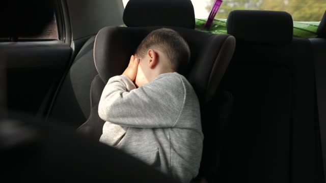 little boy sitting in car safety seat and trying to have a nap on a road trip - toddler stock videos & royalty-free footage