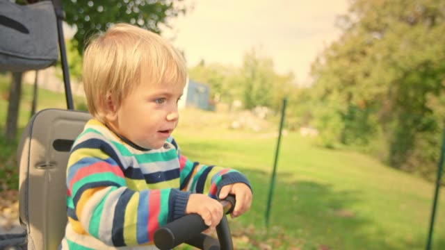 SLO MO Little boy sitting in the tricycle and pointing his finger at something in the distance