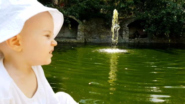 vídeos de stock, filmes e b-roll de garotinho sentado perto fonte verde no parque - só bebês meninos