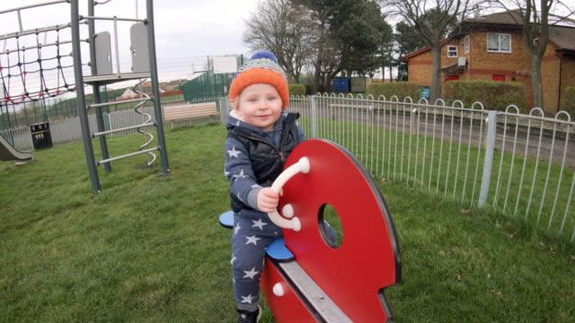vídeos y material grabado en eventos de stock de niño sentado sobre un balancín de un parque - balancín