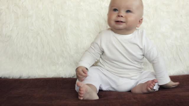 little boy sitting on a sofa - endast en pojkbaby bildbanksvideor och videomaterial från bakom kulisserna