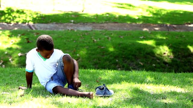 vidéos et rushes de petit garçon assis sur l'herbe enlever ses chaussures - 8 9 ans