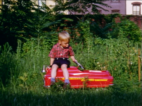 stockvideo's en b-roll-footage met 1955 home movie stop motion little boy sitting on red toy car disappears + reappears - 1955