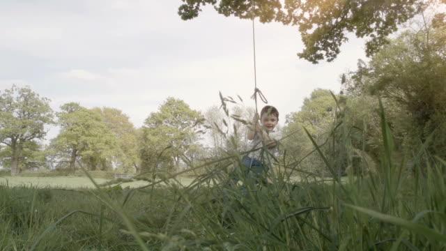 vidéos et rushes de petit garçon assis sur la corde pour se balancer dans la campagne britannique - espièglerie