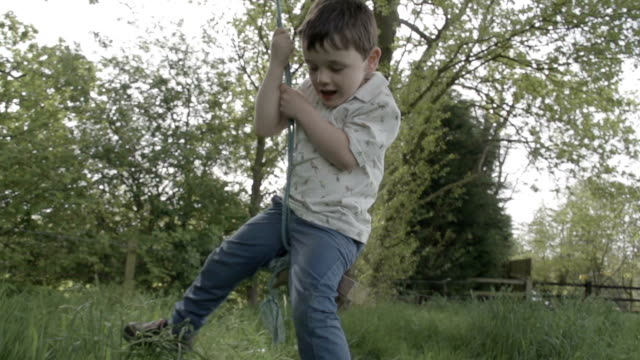 little boy sitting on rope swing in the british countryside - rope swing stock videos & royalty-free footage