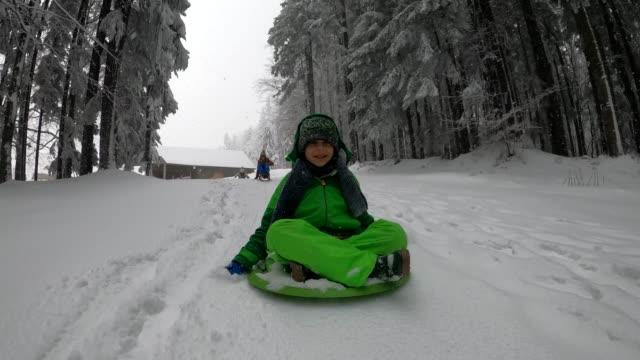 little boy sledding in winter forest. - ski jacket stock videos & royalty-free footage