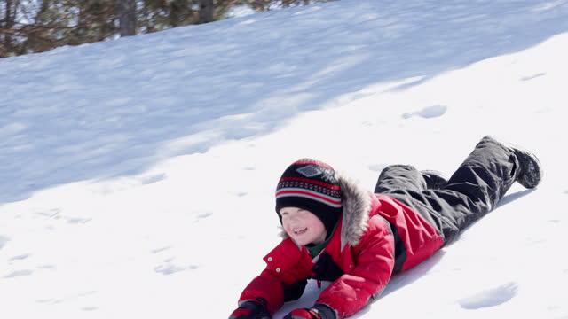 little boy sledding on the snow outdoors in winter - preschool stock videos & royalty-free footage