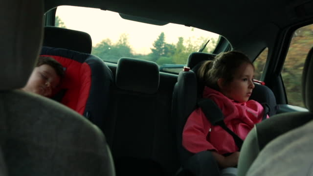 little boy sleeping in car safety seat while sister trying to have a nap on a road trip - passenger seat stock videos & royalty-free footage