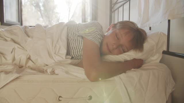 kleiner junge, der am sonnigen morgen schläft. - kopfkissen stock-videos und b-roll-filmmaterial