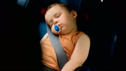 A little boy sleeps in a chair. Children's safety systems in cars.
