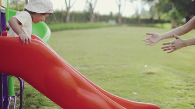 vídeos y material grabado en eventos de stock de un niño deslizándose por el tobogán en el parque con su madre en verano. - estructura metálica para niños