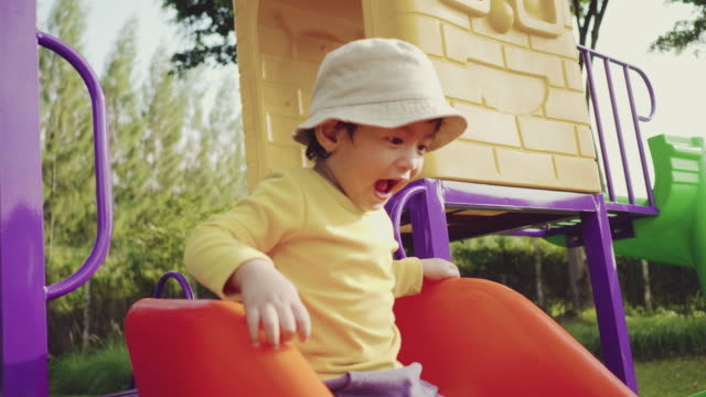 a little boy sliding down slide in park with his mother in summer. - sliding stock videos & royalty-free footage