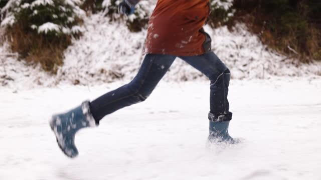 冬の森で雪に覆われた道路を滑る小さな男の子 - winter点の映像素材/bロール