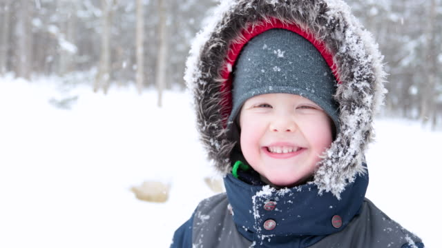 little boy smiling outdoors during winter storm. - public celebratory event stock videos & royalty-free footage