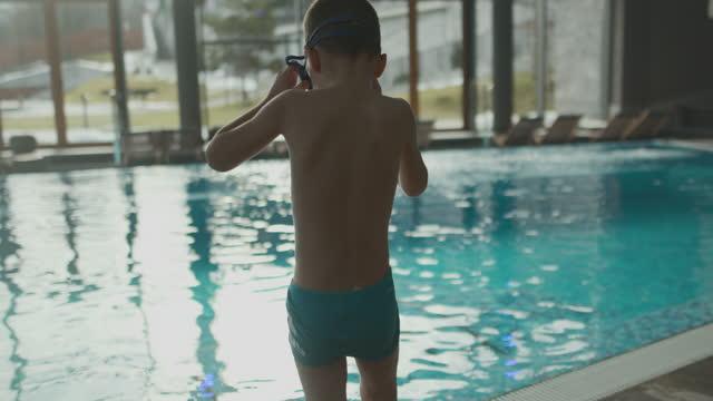 vídeos de stock e filmes b-roll de little boy spending time in hotel swimming pool - roupa de natação